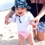 image shows a baby in a bathing suit standing in the sand