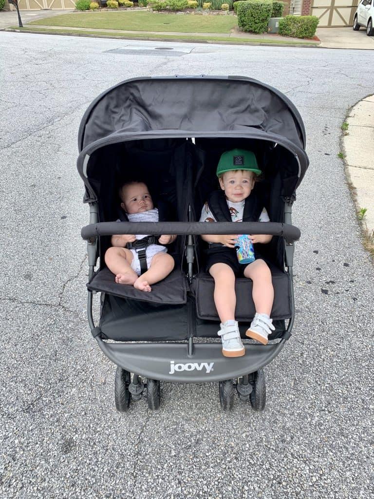 Two boys in a side by side stroller