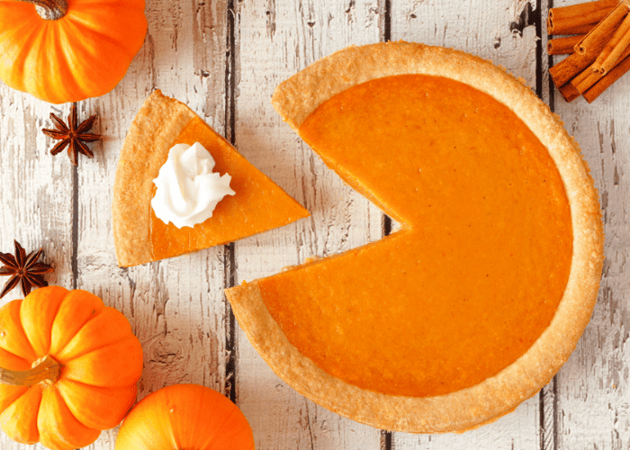 a slice of pumpkin pie on a table with pumpkins