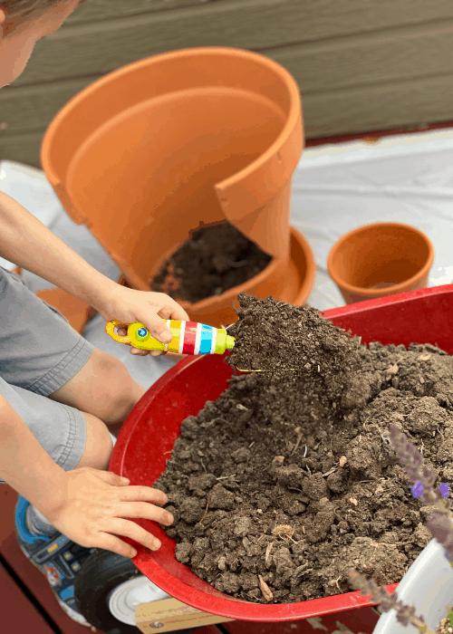 child scooping dirt